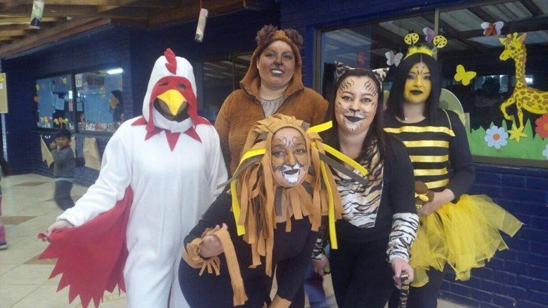 Cinco estudiantes disfrazadas de gallo, león, oso, tigre y abeja, posan sonriendo frente la cámara.