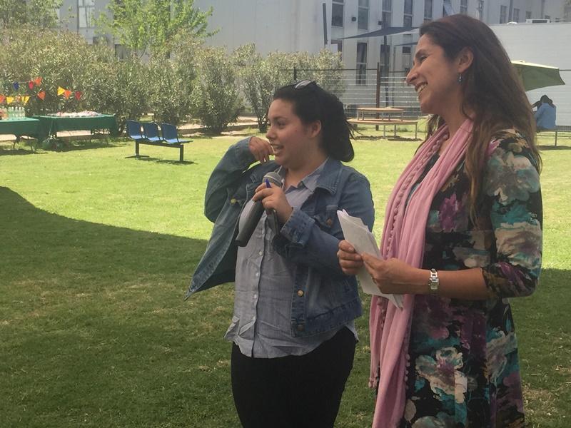 Una alumna con chaqueta de mezclilla sostiene el micrófono. A su lado una docente sostiene las tarjetas con preguntas de la trivia a la que están jugando.
