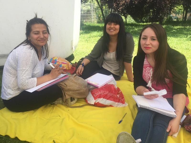 Tres alumnas están sentadas sobre una manta amarilla, en el pasto, mientras realizan una encuesta.
