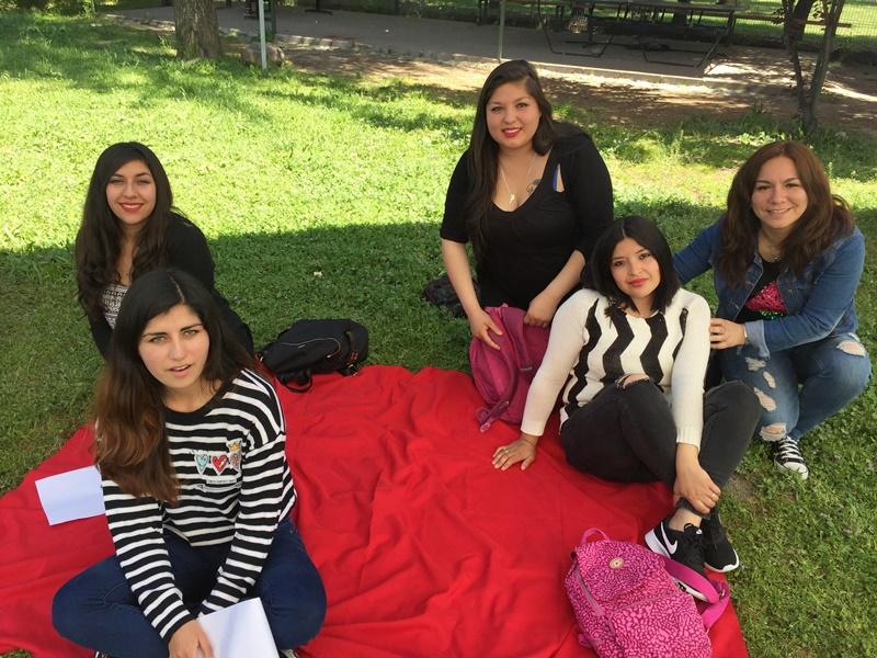 Cinco alumnas están sentadas sobre una manta roja, en el pasto, mientras realizan actividades de autoevaluación.