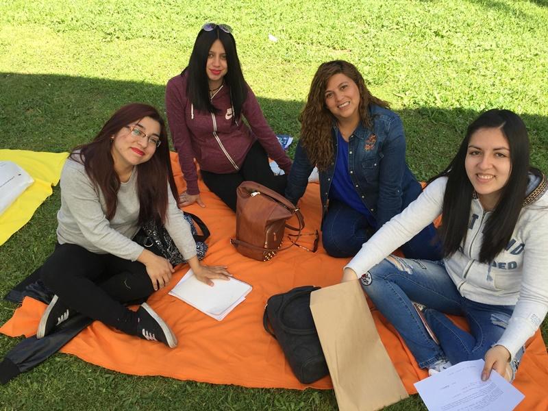 Cuatro alumnas están sentadas sobre una manta de color anaranjado, en el pasto, mientras realizan actividades de autoevaluación.