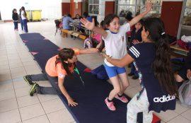 Niña completa ejercicio sonriendo sobre colchoentas, mientras la ayuda una compañera y su profesora.