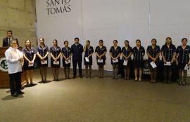 Grupo de estudiantes durante ceremonia, encabezado por Director de Escuela.
