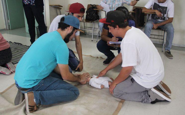 Tres alumnos realizan maniobra de reanimación a muñeco.