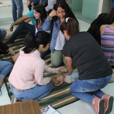 Tres participantes practican reanimación con un muñeco.