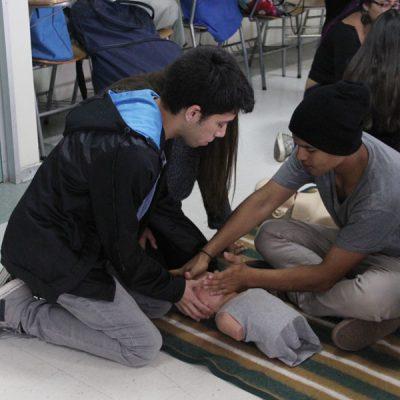 Dos alumnos realizando reanimación a muñeco.