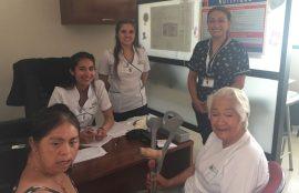 Dos estudiantes y una docente entrevistando a dos mujeres en CESFAM.