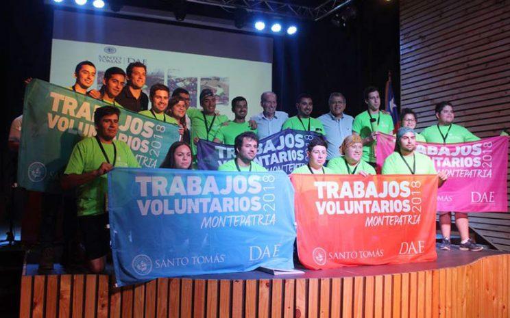 Estudiantes y autoridades sostienen banderas de los trabajos voluntarios.