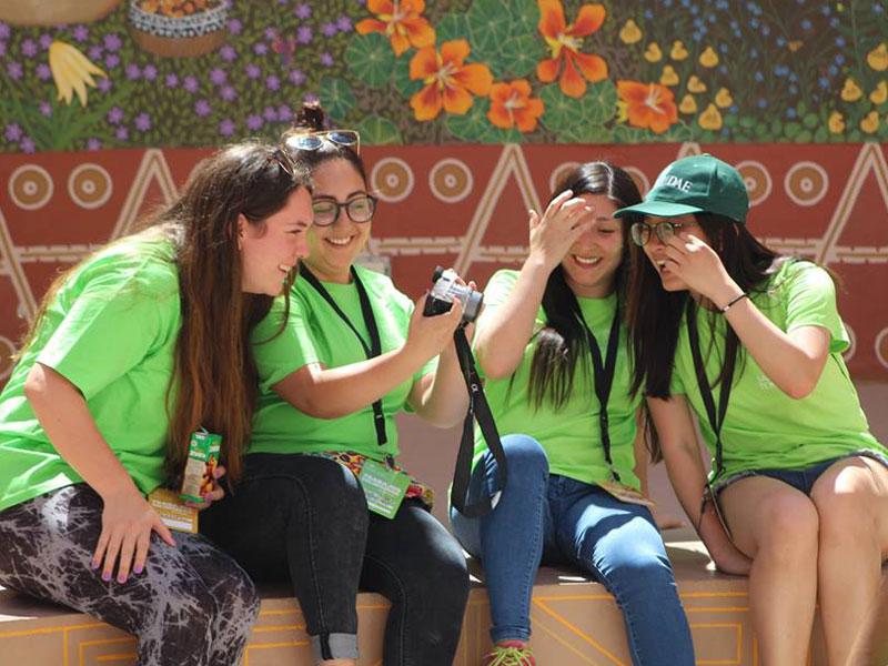 Cuatro alumnas observan su cámara fotográfica.