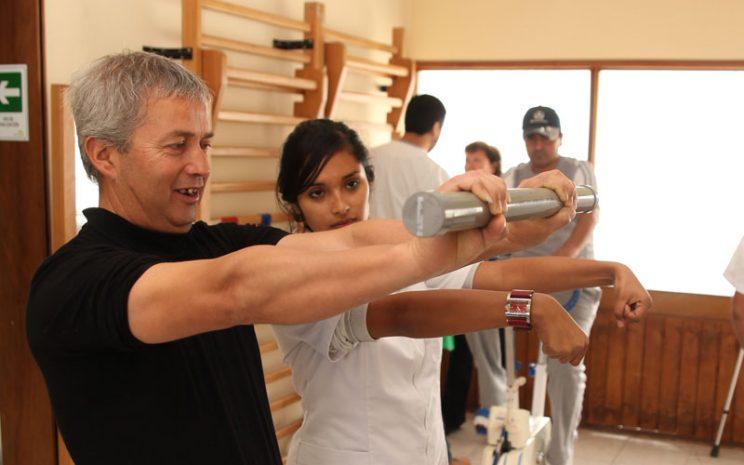 Paciente realizando ejercicio, supervisado por alumna.