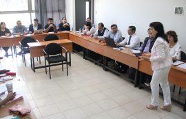 Académica dirigiéndose a los estudiantes en el aula.