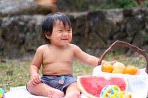 Bebé junto a canasto con frutas.
