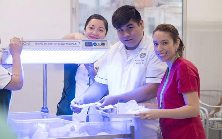Una Matrona vestida de rojo, está junto a dos estudiantes de Técnico en Enfermería y una incubadora.