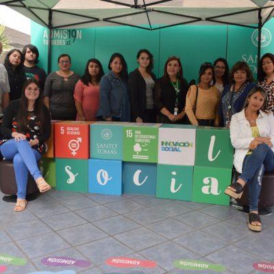 Un grupo de estudiantes posan junto unos cubos que forman la frase i social, luego de haber recibido la beca reconocimiento escolar de Santo Tomás.